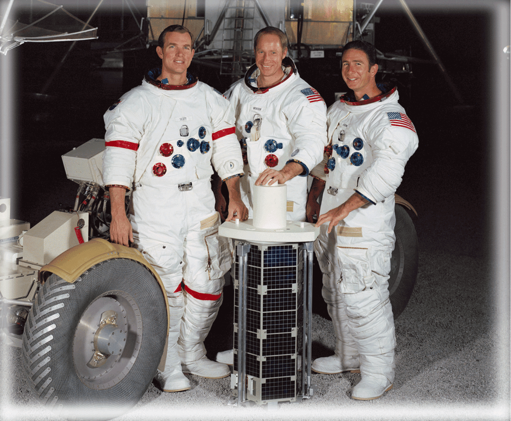 The crew of Apollo 15 pose by the subsatellite they would release into lunar orbit. Commander Dave Scott (39), Command Module Pilot Alfred Worden (39), Lunar Module Pilot James Irwin (41).